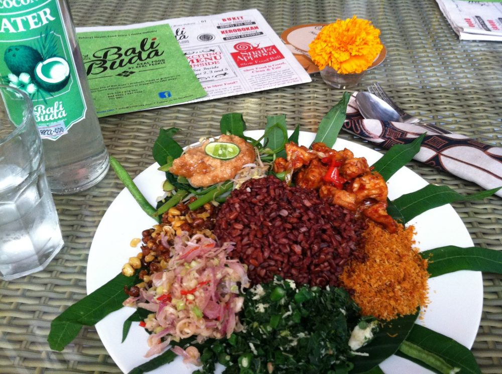 Digging into a delicious plate of vegetarian nasi campur...red rice, long beans, sambal, tempe, and roasted coconut shavings. I could't begin to tell you what those other three piles are, but it was delicious! ~in Kerobokan, Bali - Indonesia~