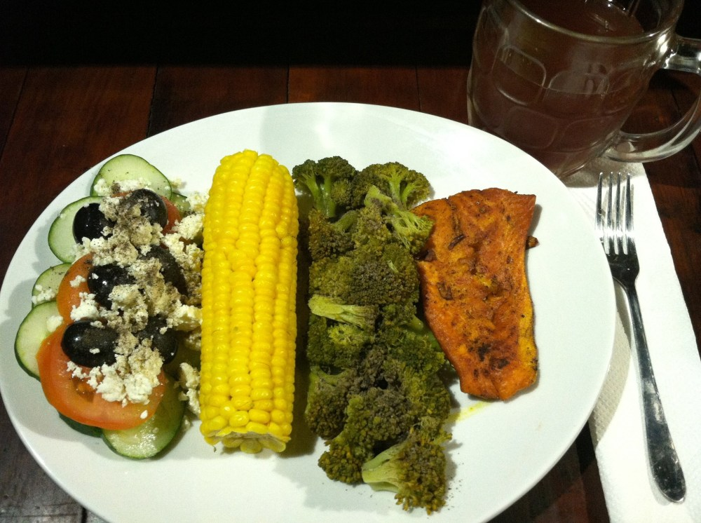 Tonight's dinner is done! Pan seared salmon, steamed broccoli, corn on the cob and a cucumber salad topped with sliced tomatoes, feta cheese & black olives. Oh and I'm washing it down with some coconut water that has a few cubes of frozen strawberry juice in it. ~in Canggu, Bali - Indonesia~